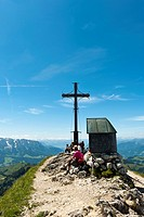 Mountain climber at the summit cross with a small chapel on Geigelstein Mountain, 1808 m, Geigelstein Nature Reserve, Aschau im Chiemgau, Upper Bavari...