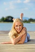 Young woman lying on a jetty at a lake in Austria.