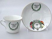 'Bone china cup and saucer manufactured by Diamond China, England. Shows the flags of the Allies, the centre vignette shows a Royal Naval battleship w...