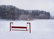 Snowfall over snow covered swing bench by Elva lake. Winter, snowdrift.