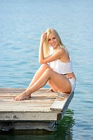 Young woman sitting on a jetty at a lake in Austria.