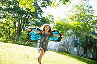 Outdoors in summer. On the farm. A child running across the lawn in front of a farmhouse, wearing large iridescent blue butterfly wings and with her a...