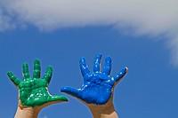 Bunt bemalte Hände vor blauem Himmel