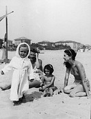 Two young women and two children on a beach in Italy.