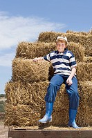 Portrait of a young boy sitting on a trailer of hay bales