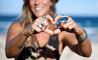 Girl at beach making love heart with fingers
