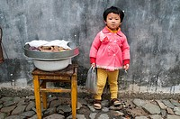 Small girl minding a tray of vegetables in Chengkan village, Huizhou, Anhui, China.