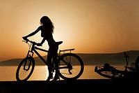 Woman with a bicycle near the sea at sunset, Koufonissi, Cyclades Islands, Greek Islands, Greece, Europe.