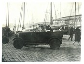 A car sits at the docks with a well-dressed woman in the front and a man in a flat cap in the back. In the background is a forest of ships' masts and ...