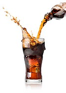Cola pouring from a bottle into a glass.