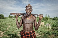 Dassanech man with kalashnikov looking after his cattle, Omo Valley, Ethiopia, Africa.
