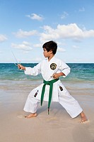 A boy practising martial arts on the beach; Honolulu, Oahu, Hawaii, United States of America