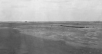 Distant view of the Wright airplane just after landing, taken from the starting point, with wing-rest in center of picture and launching rail at right...