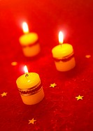 Candles burning on red patterned cloth