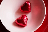 Two heart shaped candies in bowl close_up, directly above