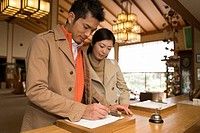 Mid Adult Couple at the Checking-in Counter in a Traditional Japanese Inn, Low Angle View, Waist Up