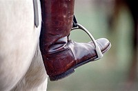Equestrian boots on stirrups.