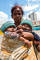 A poor beggar carrying her baby twins in the streets of Antananarivo.