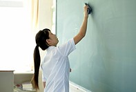 Female Student Wiping Blackboard