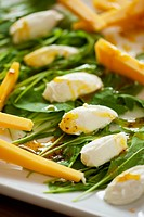 Goat cheese dumplings on rocket with savory dressing and strips of cheddar cheese