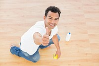 Smiling man cleaning the floor while gesturing thumbs up