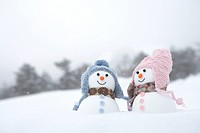 Snowman couple wearing hats and argyle scarves