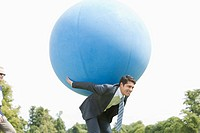 Businessman holding large ball on back