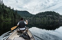 Young man fishing, Buntzen Lake, British Columbia, Canada