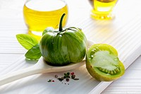 Green tomato on wooden spoon, olive oil, basil and peppercorns on wooden table