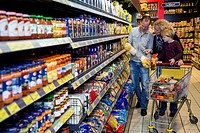 Family shopping with a shopping trolley in a supermarket, aisle with various foodstuffs, Germany