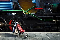 A baby carriage close to a old train in the station of the train museum of Madrid, Spain.