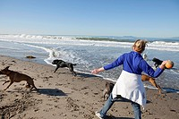 Woman aged 50+ plays ball with dogs on beach in Oxnard, California.
