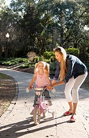 beautiful young mother and daughter riding bike and having fun outside in a park.
