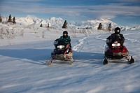 A Man And Woman Recreational Snowmobiling In Denali State Park With Mt. Mckinley And The Alaska Range In The Background, Southcentral Alaska, Spring