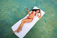 Hawaii, Oahu, Kaneohe Bay, Woman Floating On A Raft With A Tropical Drink