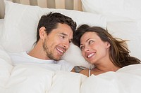 Relaxed couple lying together in bed