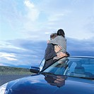 Young Couple Embracing Beside Car in Desert