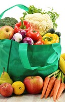 Green shopping bag with grocery products on white background.