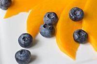 Mango (Mangifera indica) with blueberries on a plate