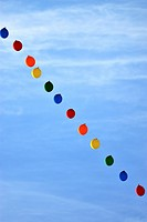 A vertical image of a string of colorful balloons floating high in the sky.