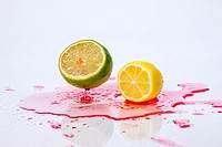 A lemon and lime are dropped onto red liquid making a splash.