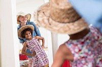 Mother and daughter looking in mirror wearing sunhats