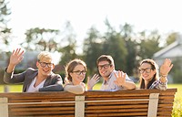 summer holidays, education, campus and teenage concept - group of students or teenagers in eyeglasses waving hands