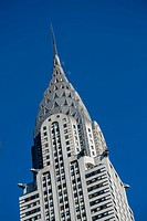 A close view of the Art Deco style architecture of the Chrysler Building in New York City against a blue sky.