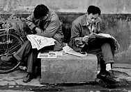 Men Reading Newspapers In A Hutong Street, Beijing China.