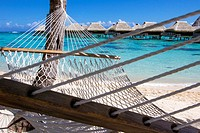 Rope hammock on a beach with overwater bungalows by the turquoise waters of Moorea in French Polynesia.
