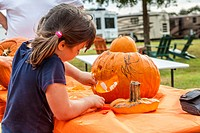 Young girl inserts teeth while decorating a pumpkin for Halloween in an RV resort park in Florida.