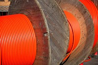 Huge orange cable drums for optic fibre connections.