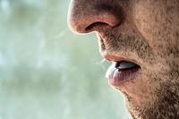 Detail of smoker male face smoking.
