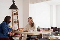 Smiling couple having breakfast at table in house